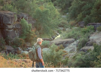 old tourist with a hand on his shoulders against the backdrop of mountains, rocks and stones, copy space