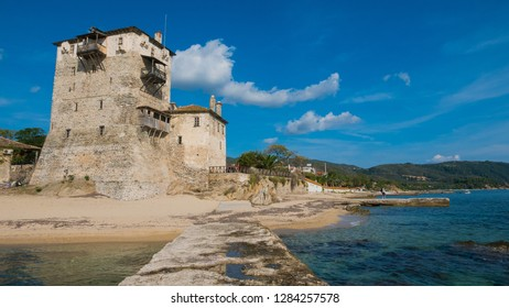 Old tower at the beach and harbor of ancient Ouranoupolis village in Greece