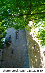 An old tower made of brick is half hidden by trees. One window in the tower has an iron balcony.