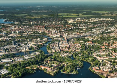"""old town Berlin Spandau with town hall, train station and """"Spandau Arcaden"""" in front, with the river Havel and Wannsee in the background"""