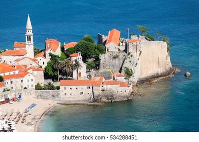 The Old Town of Budva is on peninsula in Adriatic sea. Urban beach the Ricardova Glava. Aerial view. Montenegro, Europe