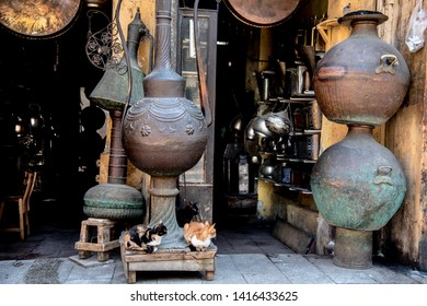 Old Town, Cairo / Egypt - 03.08.2019 Three cats sitting in front of an hardware store on a bazaar in Cairo. A lot of different teapots, kettles and lamps from tiny to giant in the background.