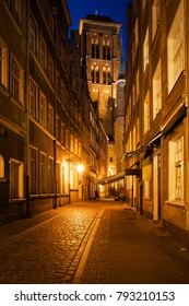 Old Town in city of Gdansk at night in Poland, Kramarska street with St Mary Church at the end.