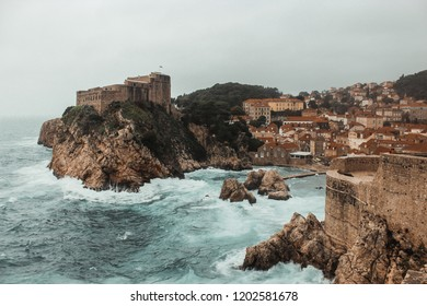 Old town Dubrovnik Croatia during moody storm with fog and waves crashing against walls of game of thrones fortress