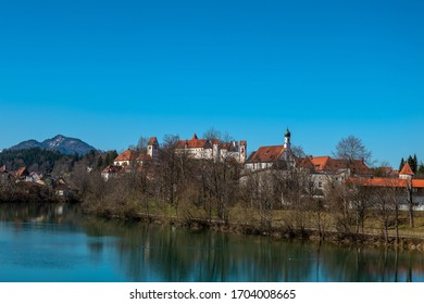 """Old town of Fuessen of the other side of the river Lech with High Castle """"Hohem Schloss"""", St. Mang with abbey and church and blue sky"""