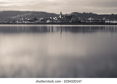 Old town of Hondarribia on atlantic coastline reflecting in ocean in long exposure black and white sepia, basque country, Spain