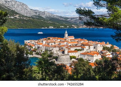 The old town of Korcula jutting out into the turquoise Adriatic on its own peninsula captured between a gap in trees on the hillside.