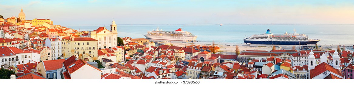 Old town of Lisbon and two cruise ships in the port at sunset. Portugal