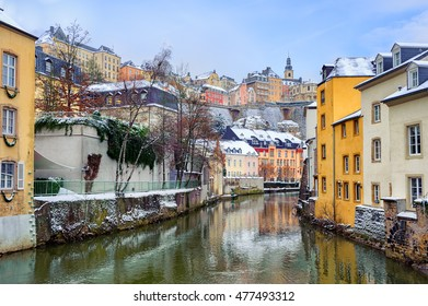 Old Town of Luxembourg and the Grund reflecting in water of Petrusse river on a snow winter day