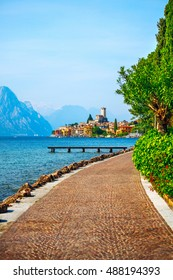Old town Malcesine on Garda lakem Veneto region. Italy. Picturesque view from embankment track made of paving stones. Sunny summer day and blue high mountains background