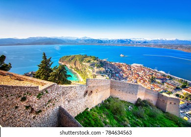 Old town of Nafplion in Greece view from above with tiled roofs, small port and bourtzi castle on the Mediterranean sea water
