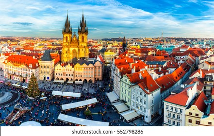 Old Town of Prague, Czech Republic. View on Tyn Church and Jan Hus Memorial on the square as seen from Old Town City Hall during Christmas market. Blue sunny sky