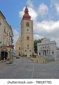 The old town of Ptuj with old street paved with stone slabs and big church in background