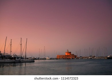 Old Town of Rhodos while pink sunset, calm sea, greek monument and harbour view. Warm colours, foggy background. Rhodos, Greece, Europe