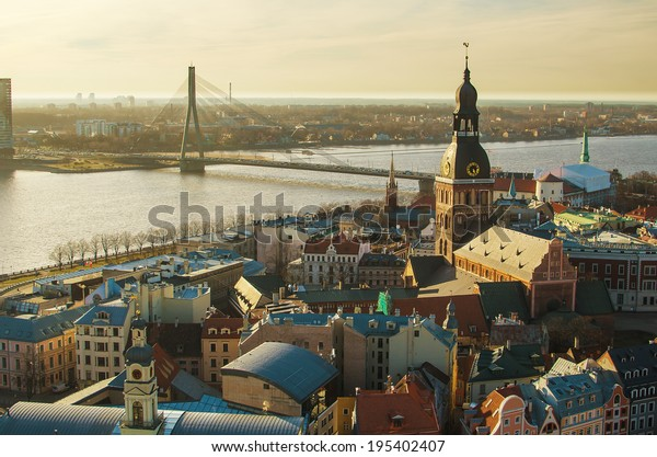 Old Town of Riga (Republic of Latvia) in the sunset. Medieval streets of the biggest city in Baltic States. Daugava river with its beautiful bridges.  Aerial amazing representative picture of the town