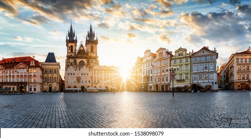The old town square of Prague, Czech Republic, during sunrise without people surounded by the historical, gothic style buildings and the famous Tyn Church