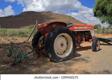old tracktor with an unknown implement at a farm stall near Drie Susters in die Great Karoo of South Africa. It serves as an attraction for kids.