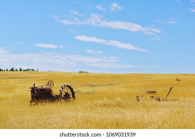 Old tractor abandoned in a field in Wyoming. The field is going golden looking grass.