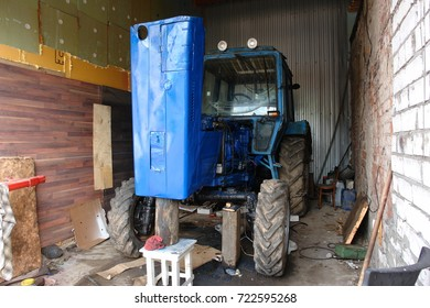 An old tractor. Agricultural machinery in the garage.
