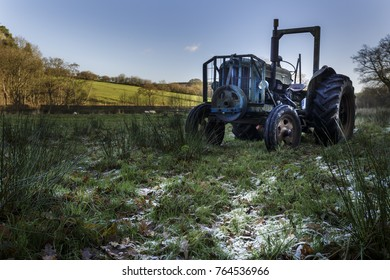 Old tractor in a field that has frost on the ground.
