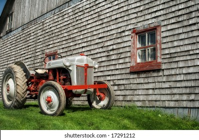 An old tractor in front of a barn