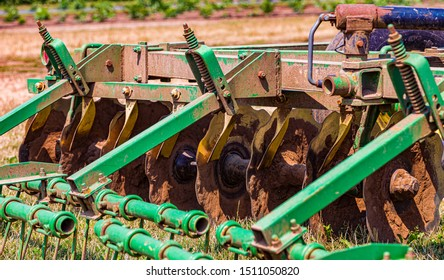 An Old Tractor Plow Laying in a Field