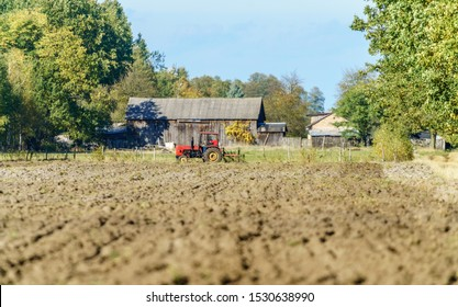 Old tractor plowing a field, wooden country building in the background