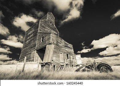 An old tractor rusts away near a grain elevator in the ghost town of Bents, Saskatchewan.  Processed with an infrared filter.