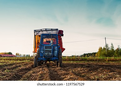 An old tractor standing still on the autumn fields of the rural Finland. The harvesting is almost done.