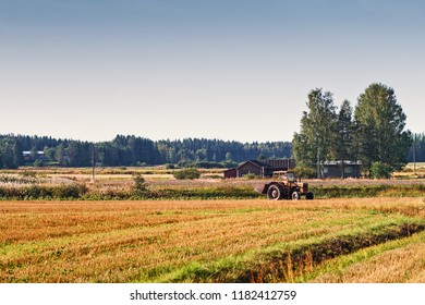 An old tractor starting the harvesting job on the field at the rural Finland. The machine seems to be quite old but it is still in use.