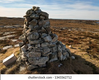 Old tradition in Norway of creating stone cairns to show the way. Rocky surroundings, low swamp vegetation. Ice cover on vegetation. Early spring. Traditional Stone Cairns with stones in Norway.