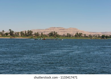 Old traditional barge boat traveling on large wide river Nile through rural countryside landscape looking to the West Bank