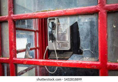 An old  traditional British red phone box that has had the window smashed.