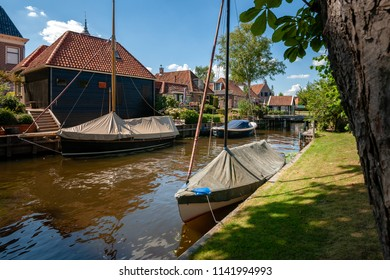 Old traditional Dutch houses along the waterfront. Water canal with sloops, sailing boats, banks and flowering gardens. Details of the village Blokzijl in the north of holland