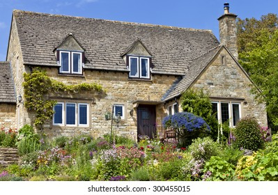 Old traditional English honey golden brown stoned cottage with colorful flowering front garden on a summer sunny day