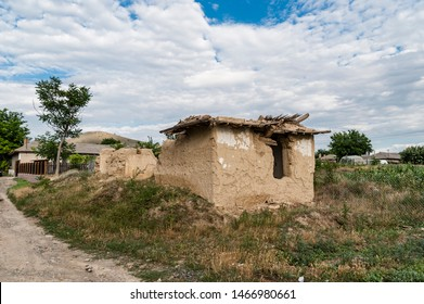 Old traditional house left in ruin with cob walls and a fallen reed roof and vegetation grown inside in a Romanian village.