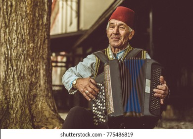 Old traditional man playing on accordion in his traditional clothes, old photos.