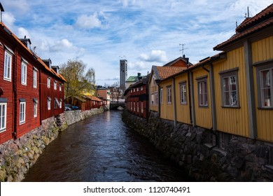 Old traditional Swedish red and yellow houses on the banks of the canal in Vasteras, shot on a spring sunny day. The Townhall can be seen far in the background.