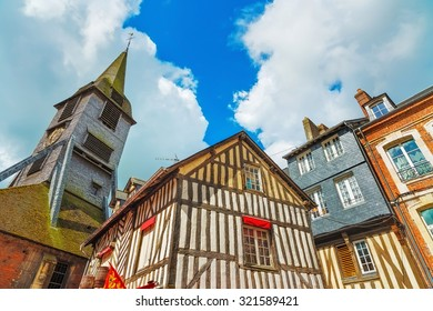 Old traditional wooden half timbered facades and church in Honfleur. Normandy, France, Europe.