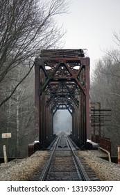 Old Train Bridge over Foggy River