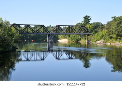 Old train bridge reflected in the Kennebec River in Brunswick, Maine