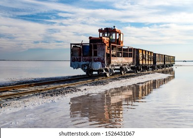 Old train rides on the railway laid in the water through the salt lake. train travels from water. Mined salt in Lake Burlin. Altai. . Bursolith. Russia. August 7, 2019