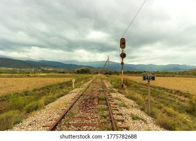 Old train track to the Alquife mine, there is a power line for the train and a traffic light, mountains and the sky is cloudy