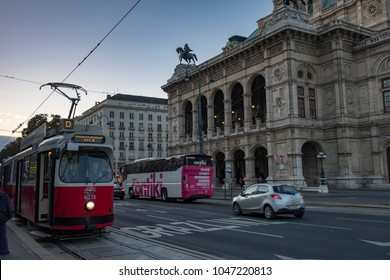 Old tram pulls away from stop with the Vienna Opera House Behind. Taken early evening in September as the city lights are coming on