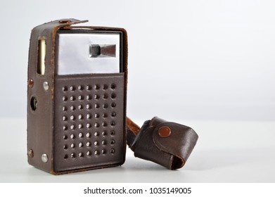 Old transistor radio in leather casing on an isolated background.