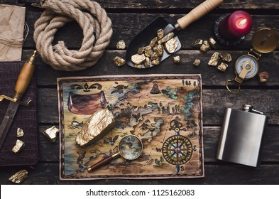 Old treasure map on adventurer or pirate table. Gold nuggets in shovel, compass, dagger, magnifying glass, rope and diary book on explorer desk.