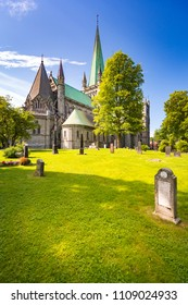 Old Trondheim cathedral. Norway, Europe travel. Blue cloudy sky in background and cemetery with green grass in foreground