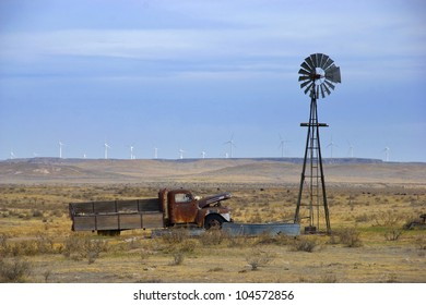 Old truck in an empty field next to an old-style windmill, with new turbine mills in the distance on the horizon