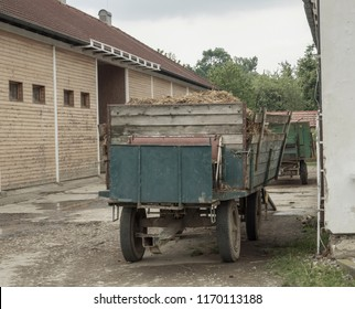 old truck with straw standing in front on barn, vintage look, faded colors