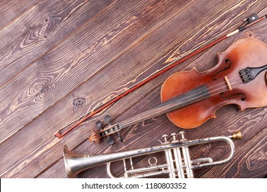 Old trumpet, violin and fiddle stick. Classical musical instruments and copy space. Retro style musical equipment.